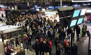 Des usagers de la SNCF rassemblés devant des écrans d'informations, à la gare  de l'Est à Paris, alors qu'un mouvement de grève des cheminots a été déclenché à  la suite de l'agression d'un contrôleur, le 6 octobre 2011.