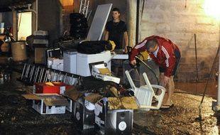 Des personnes évacuent l'eau et la boue de leur maison inondée après de fortes précipitations, le 21 octobre 2009 à Marseille.