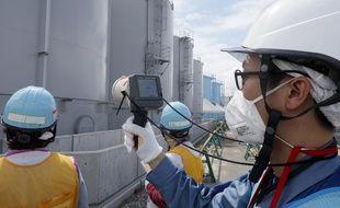 (Illustration) Sur cette photo d'archives prise le 27 juillet 2018, un membre du personnel de Tokyo Electric Power Company mesure les niveaux de rayonnement autour des réservoirs de stockage d'eau contaminée par les radiations à la centrale nucléaire de Fukushima Dai-ichi, du Tokyo Electric Power Company (TEPCO), frappée par le tsunami Okuma, préfecture de Fukushima.
