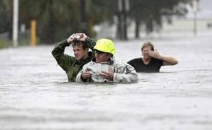 Des habitants de la Nouvelle-Orléans, en Louisianne, marchent dans une rue inondée après la passage de l'ouragan Isaac, le 29 août 2012.