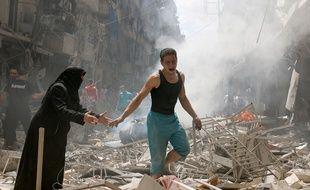Des habitants d'Alep marchent parmi les décombres après un bombardement, le 28 avril 2016.
