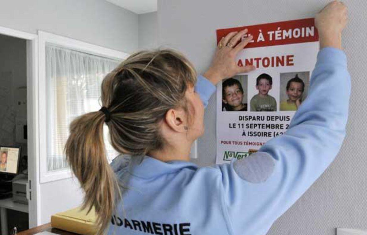 FRANCE, Brassac-les-Mines: Une gendarme colle une affiche «appel à témoin», le 11 mars 2010 sur un mur de la gendarmerie de Brassac-les-Mines, un an et demi après la disparition du petit Antoine à Issoire, le 11 septembre 2008. – THIERRY ZOCCOLAN / AFP