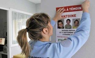 FRANCE, Brassac-les-Mines: Une gendarme colle une affiche «appel à  témoin», le 11 mars 2010 sur un mur de la gendarmerie de  Brassac-les-Mines, un an et demi après la disparition du petit Antoine à  Issoire, le 11 septembre 2008.
