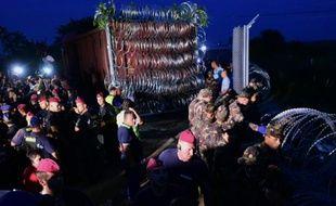 Des militaires de l'armée hongroise terminent de mettre en place la clôture de barbelée haute de deux mètres barrant la frontière serbo-hongroise près de Röszke, le 14 septembre 2015