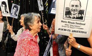 La mère d'une victime de la dictature argentine se tient à côté d'une pancarte avec la photo de Mario Alfredo Sandoval, lors d'une manifestation le 9 avril 2014 à Buenos Aires pour réclamer son extradition de France