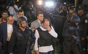Le Français Christophe Naudin (c), est escorté par des forces de police lors de son arrivée en République Dominicaine, le 4 mars 2016 à Saint-Domingue.