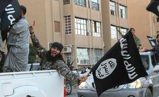 Un membre supposé du groupe Etat islamique paradant un drapeau à la main dans les rues de Raqqa en Syrie le 30 juin 2014. (image d'illustration)