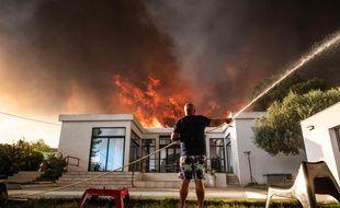 Un habitant tente de protéger sa maison des flammes à La Couronne, près de Marseille, mardi 4 août.