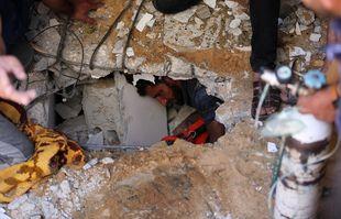 Les Palestiniens recherchent des victimes sous les décombres d'un bâtiment détruit dans le quartier résidentiel de Rimal, à Gaza, à la suite d'un bombardement massif israélien sur l'enclave contrôlée par le Hamas, le 16 mai 2021.