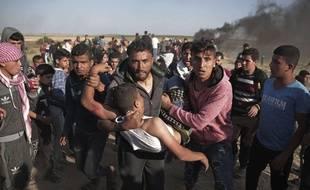 Des manifestants palestiniens portent un homme touché par les tirs de l'armée israélienne pendant une manifestation à Gaza le 31 mars 2018.
