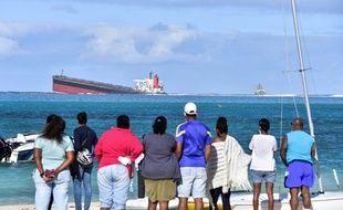 Des Mauriciennes et des Mauriciens observent le navire échoué à proximité du site naturel de Blue Bay, jeudi 6 août 2020.