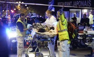 Une victime de l'attaque de la salle du Bataclan à Paris évacué par les services de secours, le 14 novembre 2015