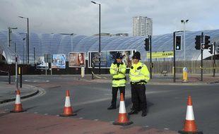 Des policiers surveillent les abords de la Manchester Arena, au lendemain de l'attentat terroriste qui a fait au moins 22 morts.