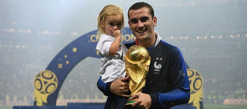 Antoine Griezmann pose avec sa fille Mia après la victoire lors de la Coupe du monde 2018.