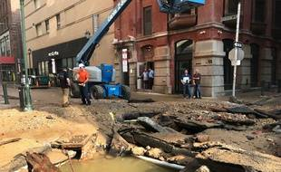 Le personnel du département des eaux de la ville de Philadelphie travaille après que la rupture des canalisations principales de la ville a entraîné une inondation mardi 3 juillet 2018.