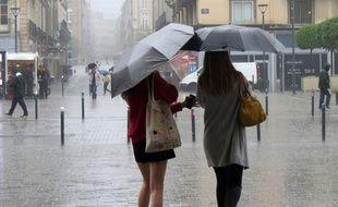Image de deux femmes marchant sous la pluie.
