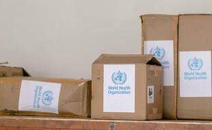 Des cartons portant le logo de l'Organisation mondiale de la santé (OMS).