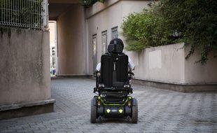 Une personne handicapée en fauteuil roulant électrique (illustration).