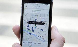 Un client consulte le 17 juin 2015 à Paris l'application UberPop pour commander une voiture
