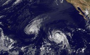 Image satellite prise le 6 août 2014 de l'ouragan Iselle, au centre, et de la tempête tropicale qui s'est transformée en ouragan, Julio, à droite. (AP Photo/NOAA)/NY107/842111306576/