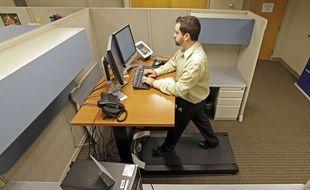 Josh Baldonado, assistant administratif pour une compagnie d'assurances, travaille en marchant sur un tapis roulant devant son bureau, le 28 août 2013.