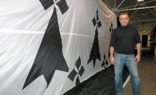 Jean Bourrassier devant le drapeau breton géant confectionné par sa société.