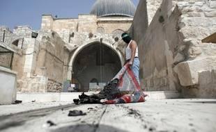 Un Palestinien masqué par un bandeau du Hamas sort un apis brûlé de la mosquée Al-Aqsa, à Jerusalem, après une intervention de la police israélienne, le 13 septembre 2015.