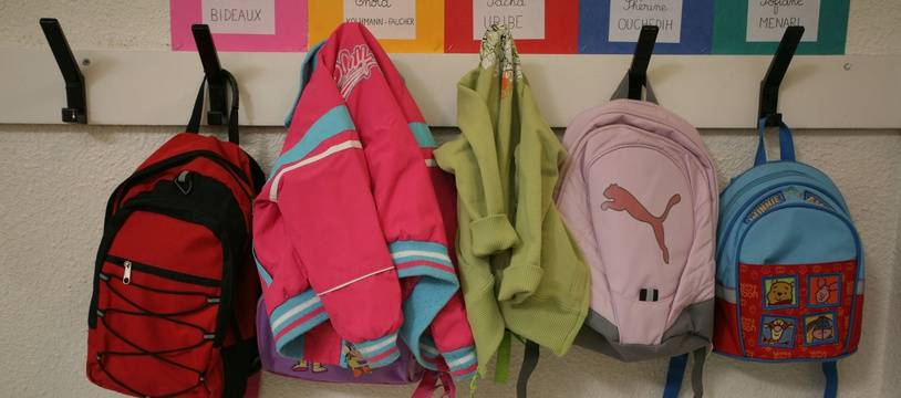 Premier jour de rentrée scolaire dans une école maternelle de Toulouse et petits sacs d'écolier suspendus a un porte-manteau (illustration).