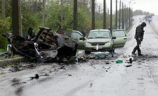 Un expert examine les lieux d'un bombardement qui a fait 4 morts, près d'un point de contrôle séparatiste d'Olenivka, dans l'est de l'Ukraine, le 27 avril 2016