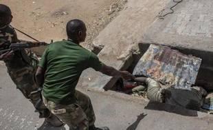 Un soldat nigérian découvre un cadavre en décomposition dans un égout dans la ville de Bama (nord du Nigéria), le 25 mars 2015