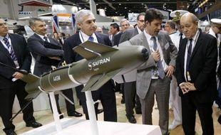 Le ministre de la Défense Jean-Yves Le Drian (d) de passage au stand Sagem du groupe Safran lors d'un salon international de la Défense à Abou Dhabi le 22 février 2015