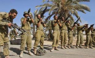 Des soldats israéliens déchargent leurs armes près de la frontière entre Israël et la Bande de Gaza après leur retrait de l'enclave palestinienne, le 4 août 2014