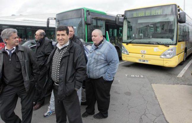 Des chauffeurs de bus de la compagnie des Courriers de l'Ile-de-France (CIF) se tiennent près de bus au siège d'une des entreprises de transport en commun de Villepinte, le 2 avril 2010.