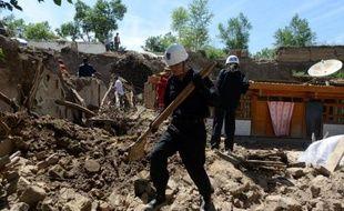 Des secouristes chinois fouillent les décombres d'une maison dévastée par un tremblement de terre le 23 juillet 2013 à Dingxi