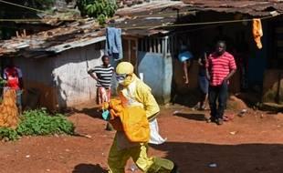 Le corps d'un enfant victime d'Ebola emporté pour son inhumation par un membre de la Croix Rouge, le 12 novembre 2014 à Freetown