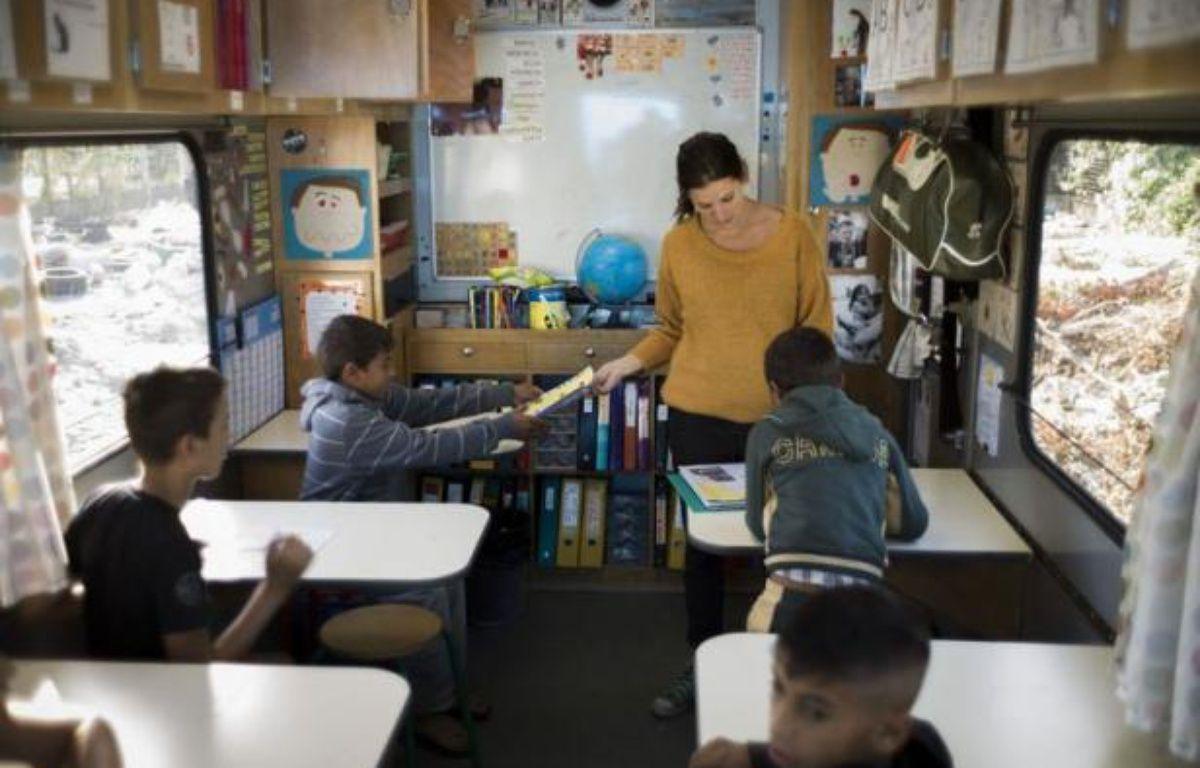 """""""Bonjour, on vient chercher les enfants pour l'école!"""". C'est la rentrée jeudi au bidonville de La Courneuve où vivent un millier de Roms. Trois enseignants font classe dans des camions colorés, dans l'espoir d'inscrire un jour les élèves dans une école en dur. – Fred Dufour afp.com"""
