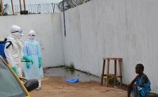 Une jeune fille pleure la mort de son père et de sa mère infectés par le virus Ebola, devant le nouveau centre de traitement de l'épidémie à Monrovia (Libéria), le 23 septembre 2013