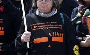 Une syndicaliste française portant un tee-shirt avec la mention: «22 000 emplois supprimés en 3 ans. France Télécom doit être condamné» au début du procès du groupe français France Télécom, devant le tribunal de Paris, le lundi 6 mai 2019.