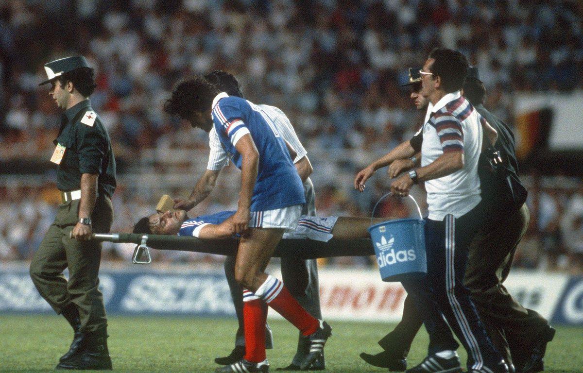 Michel Platini s'inquiète de la santé de son partenaire Patrick Battiston, inconscient après avoir été violemment percuté par le gardien allemand Harald Schumacher, le 8 juillet 1982 à Séville. – STAFF / AFP