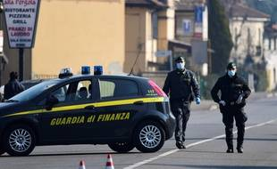 Des policiers italiens, avec des masques, contrôlent les entrées de la ville de Zorlesco, au sud est de Milan le 24 février 2020, pendant l'épidémie de coronavirus.