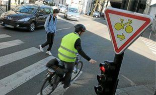 Les cyclistes peuvent tourner à droite et griller les feux rouges signalés par un panneau.