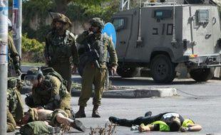 Des soldats israéliens portent secours à un des leurs (g) alors que le corps du palestinien auteur du coup de couteau gît au sol (d) à l'entrée d'Hébron en Cisjordanie occupée, le 16 octobre 2015