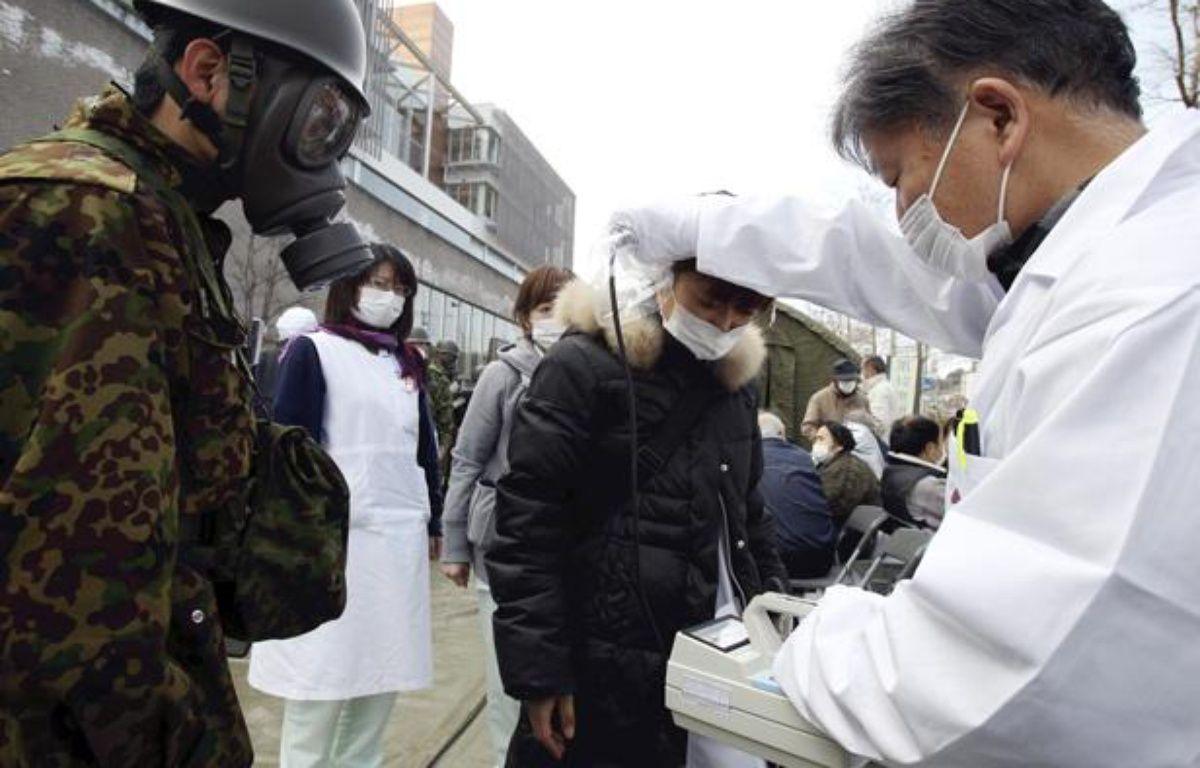 Un médecin mesure le degré d'exposition aux radiations grâce à un compteur Geiger, près de Fukushima le 13 mars 2011. – AFP PHOTO / YOMIURI SHIMBNUN
