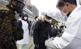 Un médecin mesure le degré d'exposition aux radiations grâce à un compteur Geiger, près de Fukushima le 13 mars 2011.