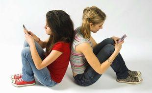 : Adolescentes envoyant des SMS avec leurs téléphones portables
