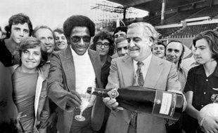 Paulo César sable le champagne après avoir signé un contrat à l'OM, avec le président du club Fernand Méric, le 11 juillet 1974.