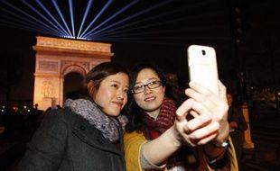 Des touristes chinoises prennent un selfie avec leur téléphone sur les Champs-Elysées le 31 décembre 2014