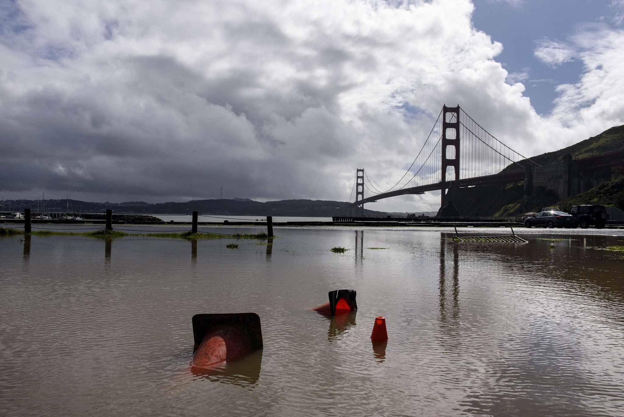 Safety cones float in a puddle in the Horseshoe Bay parking lot as storm clouds hang over the Golden Gate Bridge, in Sausalito, Calif., Thursday, Feb. 14, 2019. Waves of heavy rain pounded California on Thursday, filling normally dry creeks and rivers with muddy torrents, flooding roadways and forcing residents to flee their homes in communities scorched by wildfires. (AP Photo/Michael Short)/FX435/19045806820080/1902150050