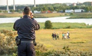 Un gendarme filme des migrants cherchant à s'intruire dans l'Eurotonnel pour passer en Angleterre, le 30 juillet 2015 à Coquelles, près de Calais