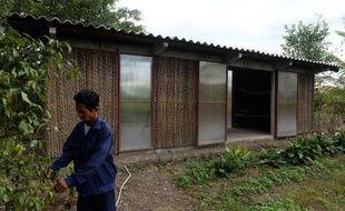 Vo Van Dong, agriculteur, devant sa maison prototype en bambou et feuilles de cocotier le 11 décembre 2014 à Long An, dans le delta du Mékong